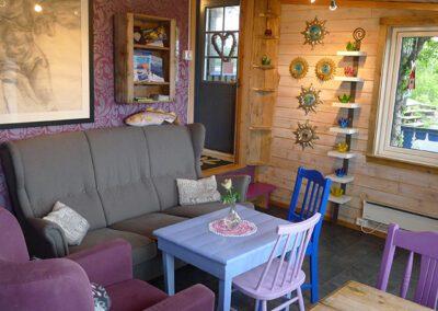 Sofa, stoler og bord. Stort bilde på veggen. Ytterdør og vindu.